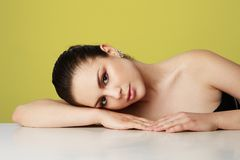 Beautiful young woman with big brown eyes and dark eyebrows relaxing over empty yellow studio background.Model with. Light nude make-up.Copy paste space,close stock image