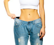 Beautiful young woman with big jeans Stock Images