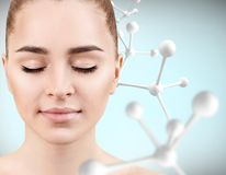Young woman with big white molecule chain. Beautiful young woman with big white molecule chain over gray background. Innovation cosmetics concept Stock Photo