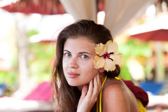 Beautiful young woman with big yellow flower in Royalty Free Stock Photo