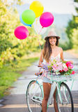 Beautiful young woman on bike. In park with balloons Royalty Free Stock Photography