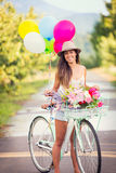 Beautiful young woman on bike. In park with balloons Royalty Free Stock Images