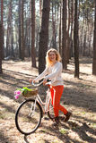 Beautiful young woman on bike in sunny park Stock Photo