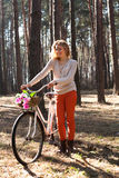 Beautiful young woman on bike in sunny park Stock Image
