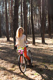 Beautiful young woman on bike in sunny park Stock Photography