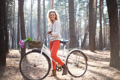 Beautiful young woman on bike in sunny park Royalty Free Stock Photo