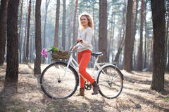 Beautiful young woman on bike in sunny park Stock Photos