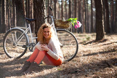 Beautiful young woman on bike in sunny park Stock Images