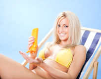 Beautiful young woman in bikini applying suncream Stock Image