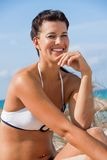 Beautiful young woman in a bikini on the beach. Beautiful young woman with a lovely friendly warm smile sitting in a bikini on the beach on a sand dune Stock Photo