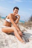 Beautiful young woman in a bikini on the beach. Beautiful young woman with a lovely friendly warm smile sitting in a bikini on the beach on a sand dune Royalty Free Stock Photo