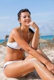 Beautiful young woman in a bikini on the beach. Beautiful young woman with a lovely friendly warm smile sitting in a bikini on the beach on a sand dune Stock Images
