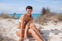Beautiful young woman in a bikini on the beach. Beautiful young woman with a lovely friendly warm smile sitting in a bikini on the beach on a sand dune Stock Photos