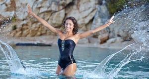 Beautiful young woman in bikini on the beach. Splashing water Royalty Free Stock Images