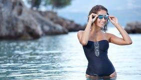 Beautiful young woman in bikini on the beach. Splashing water Stock Photo