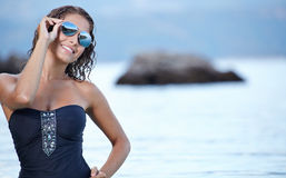 Beautiful young woman in bikini on the beach. Splashing water Royalty Free Stock Photography