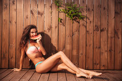 Beautiful young woman in bikini eating watermelon over wooden background Stock Photography