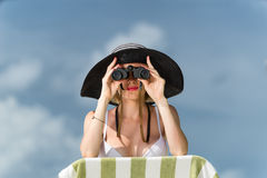 Beautiful young woman in bikini looking through binoculars at th Stock Photography