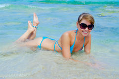 Beautiful young woman in bikini lying down. And smiling in sea at the resort Stock Photography