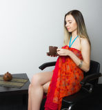Beautiful  young woman in bikini and pareo sitting on a chair and drinking coffee in brown cup Stock Photo
