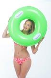 Beautiful young woman in bikini posing with a big green rubber ring Stock Photography