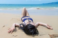 Young woman in bikini relaxing on the beach. Beautiful Young woman in bikini relaxing on the beach royalty free stock images