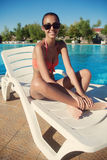 Beautiful young woman in bikini relaxing swimming pool. Beautiful young woman in bikini relaxing by swimming pool Royalty Free Stock Photography
