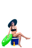 Beautiful young woman in bikini sits in a cooler bag. Beautiful young woman sits on a cooler bag with a large rubber ring Royalty Free Stock Image