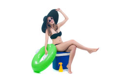 Beautiful young woman in bikini sits in a cooler bag. Beautiful young woman sits on a cooler bag with a large rubber ring Royalty Free Stock Images