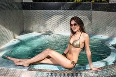 Beautiful young woman in bikini sitting on the edge of the swimming pool Royalty Free Stock Photography