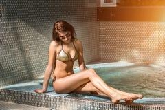 Beautiful young woman in bikini sitting on the edge of the swimming pool Stock Image