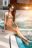 Beautiful young woman in bikini sitting on the edge of the swimming pool royalty free stock images