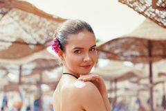 Beautiful young woman in bikini smear protective cream on the skin on the beach under the sun. Sexy Young Woman in Bikini  Holding  Bottles of Sunscreen in Her stock photo