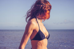 Beautiful young woman in bikini standing on the beach Stock Image