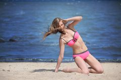Beautiful young woman in bikini on the sunny beach Stock Photo