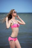 Beautiful young woman in bikini on the sunny beach Stock Images