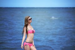 Beautiful young woman in bikini on the sunny beach Stock Image