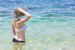 Beautiful young woman in bikini on the sunny tropical beach. The side view of a beautiful woman in a bikini wearing a sunhat and relaxing in the water at a sunny Stock Image