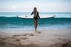 Beautiful young woman in bikini with surf board at beach of tropical island. royalty free stock images