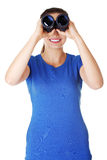 Beautiful young woman with binoculars. Royalty Free Stock Photography