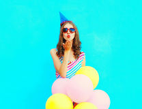 Beautiful young woman in a birthday cap is sends an air kiss holds an air colorful balloons on a blue. Background Stock Photo