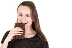 Beautiful young woman biting a chocolate bar. A beautiful young woman biting a chocolate bar royalty free stock images