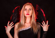 Beautiful young woman with black angel wings Stock Images
