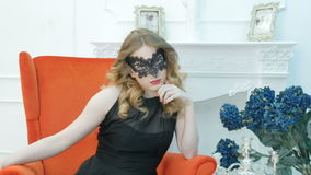 Beautiful young woman in a black carnival mask, at a party, in a red armchair. stock video footage