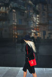 Beautiful young woman in a black coat and hat, wearing red glasses and a red bag walking in the city. Reflection of the Royalty Free Stock Photography