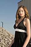 Beautiful young woman in black dress. Beautiful young fashion model in a black dress poses in industrial setting stock image
