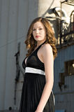 Beautiful young woman in black dress. Beautiful young fashion model in a black dress poses in industrial setting stock photo