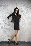 Beautiful young woman in a black dress on abstract gray background Royalty Free Stock Photos