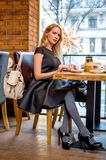 Beautiful young woman sitting at the table at cafe Stock Photos