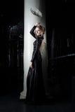 Beautiful young woman in black dress near column royalty free stock image
